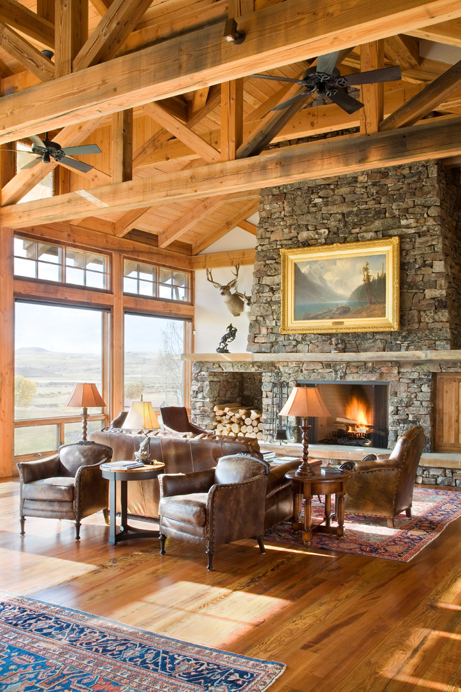 rustic cottage home wood beams big stone rock fireplace leather sofa chairs persian carpet deet antlers on wall better decorating bible blog inside home