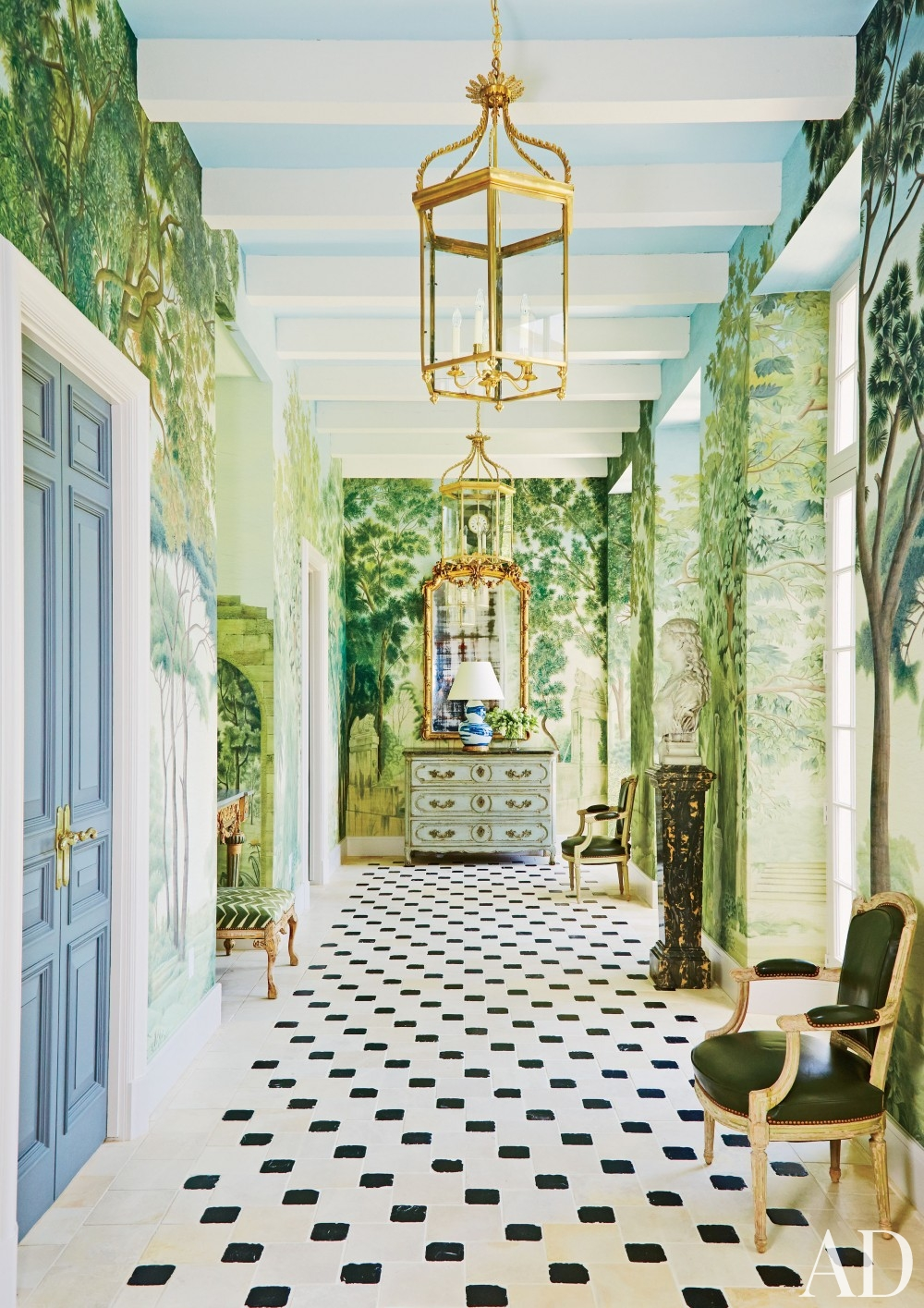 wall mural plants leafy greens checkered floor decorating sun room blue ceiling blue painted double doors french revival style green leather upholstered louis chair gold gilded mirror better decorating bible blog