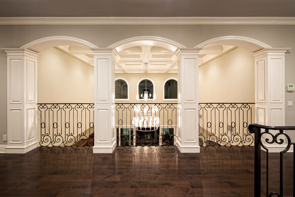mediterranean-hallway open to below wrought iron railing dark hardwood strip floors chandelier